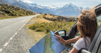 Portrait of young woman in car looking at map © swissmediavision/GettyImages