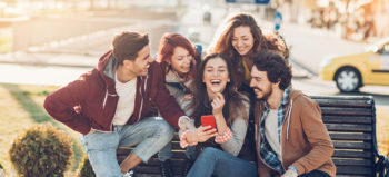 Group of friends watching at a smart phone and laughing _Quibi